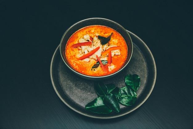 Ampio colpo selettivo di zuppa di pesce piccante in una ciotola su un piatto