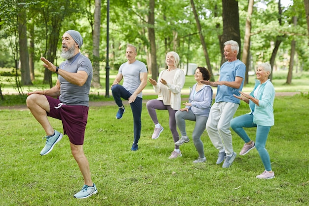Wide shot of active elderly men and women doing morning workout in park with senior trainer