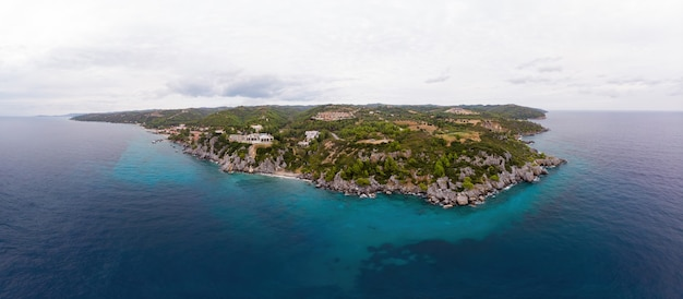 Wide shot of the aegean sea coast of greece, loutra buildings located near the rocky cliffs, greenery and blue water. view from the drone