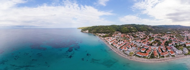 Wide shot of the aegean sea coast of greece, skala fourkas buildings located near the rocky cliffs, greenery and blue water. view from the drone