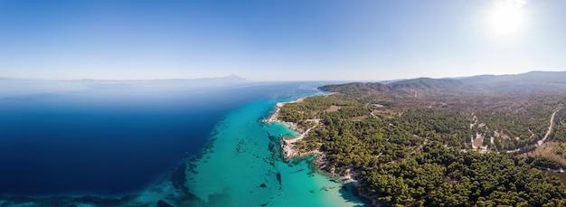 Campo lungo della costa del mar egeo con acqua blu trasparente, vegetazione intorno, vista di pamorama dal fuco, grecia
