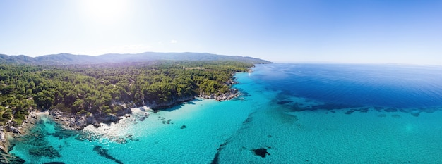Wide shot of the aegean sea coast with blue transparent water, greenery around, pamorama view from the drone, greece
