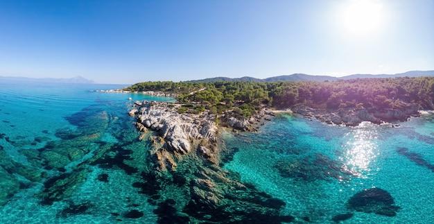 Ripresa a tutto campo della costa del mar egeo con acqua blu trasparente, vegetazione intorno, rocce, cespugli e alberi, colline, vista di pamorama dal drone, grecia