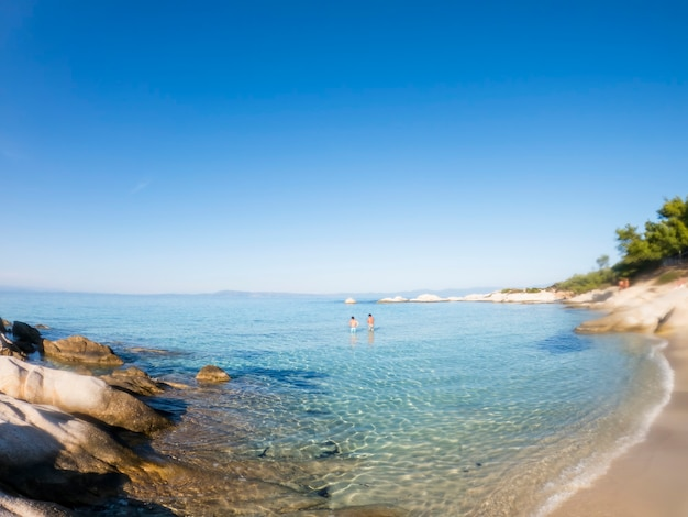 Wide shot of a aegean sea coast with people in the blue water, rocks near the shore, greece