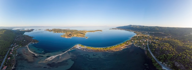 Wide shot of the aegean sea coast with a town on the shore and island, blue transparent water, greenery around, pamorama view from the drone, greece