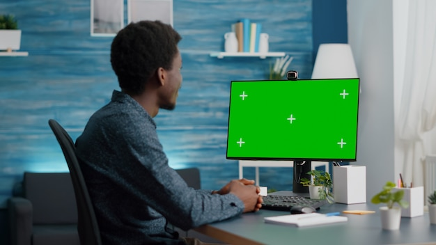 Wide shot of african american man talking on video call on computer with mock up chroma display isol...
