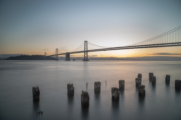 Wide shot of bay bridge on the body of water during sunrise in san francisco, california