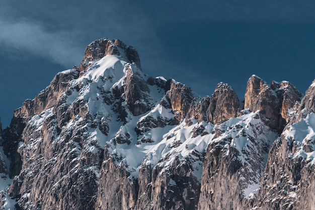 Wide shot of a big mountain formation with snow covering some parts of it and a blue sky