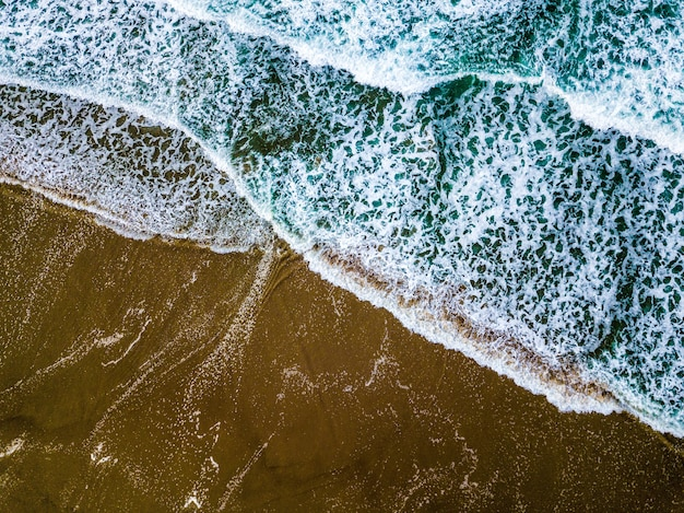 Panoramica delle onde blu del mare su una spiaggia sabbiosa