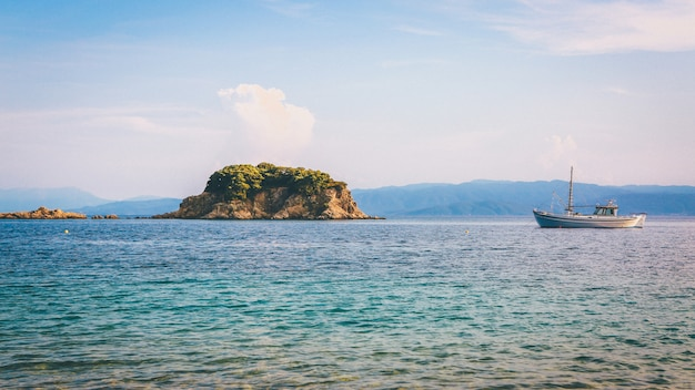 Wide shot of a boat and a green cliff on the body of water under a clear blue sky