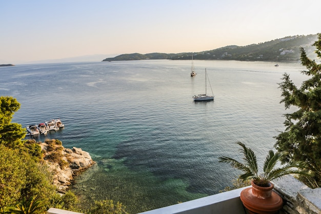 Wide shot of boats on the body of water surrounded by mountains and green plants in skiathos, greece