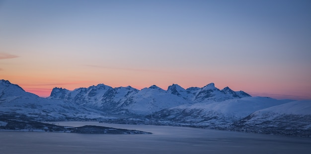 Wide shot of the breathtaking snow covered mountains captured in tromso, norway