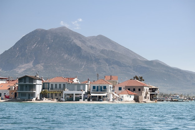 Wide shot of buildings on the shore of the beach with mountains at northern greek