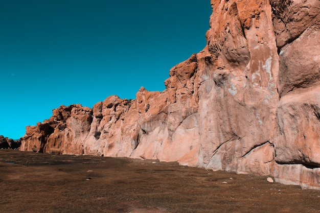 Wide shot of cliffs surrounded by land with a blue sky on a sunny day
