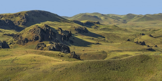Wide shot of empty grassy hills with a blue sky in the background at daytime