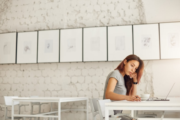 Wide shot of female worker or student doing her daily job designing prints online or studying in a bright studio environment. education concept.