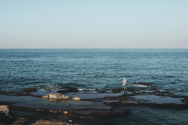 Wide shot of a fisherman standing on the shore during daytime
