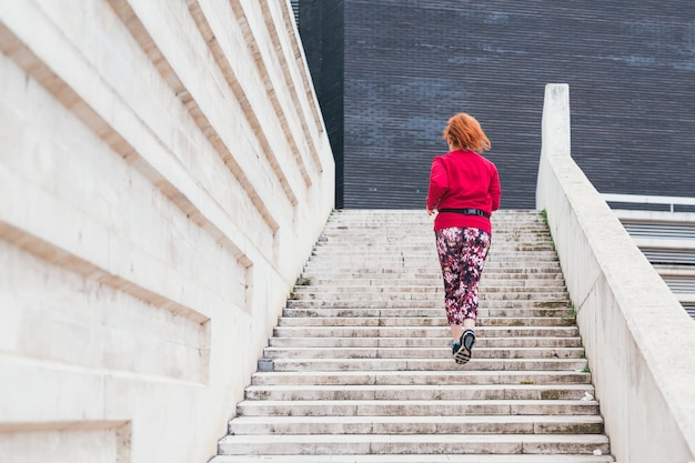 A wide shot from behind of a sporty red-haired caucasian female running up stairs outdoor