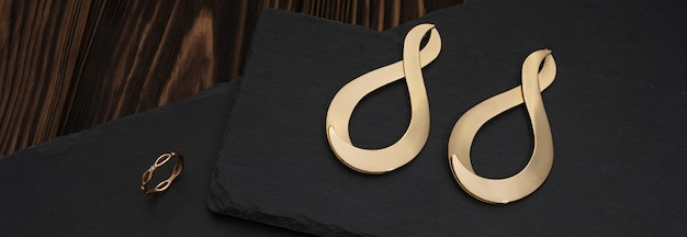 Wide shot of golden infinity symbol shape earrings and ring on dark stone surface