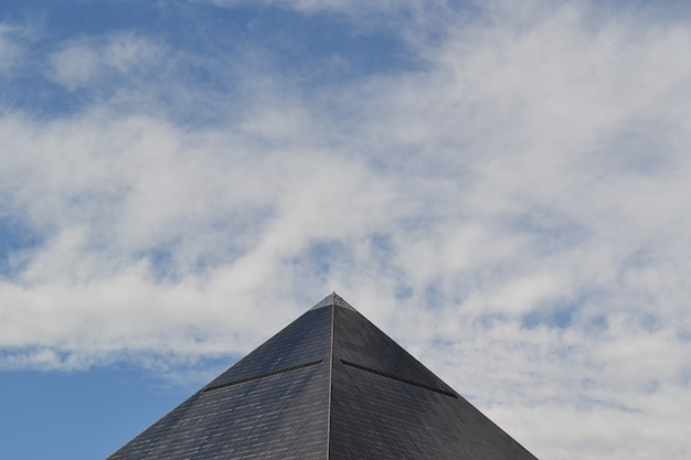 Wide shot of a gray egyptian pyramid in las vegas, california under a blue sky with clouds