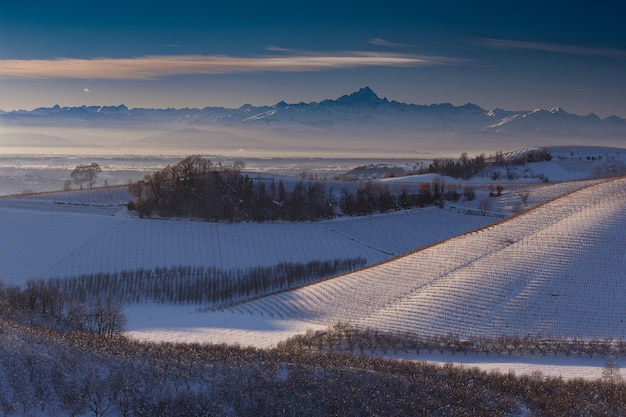 Wide shot of hills covered with snow in langhe piedmont italy