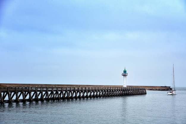 Wide shot of a long pier in the sea under the beautiful blue sky
