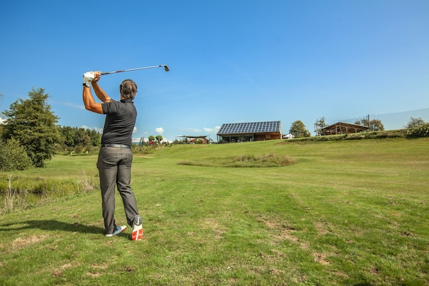 Wide shot of a male athlete swinging a golf club on a sunny day in a golf course