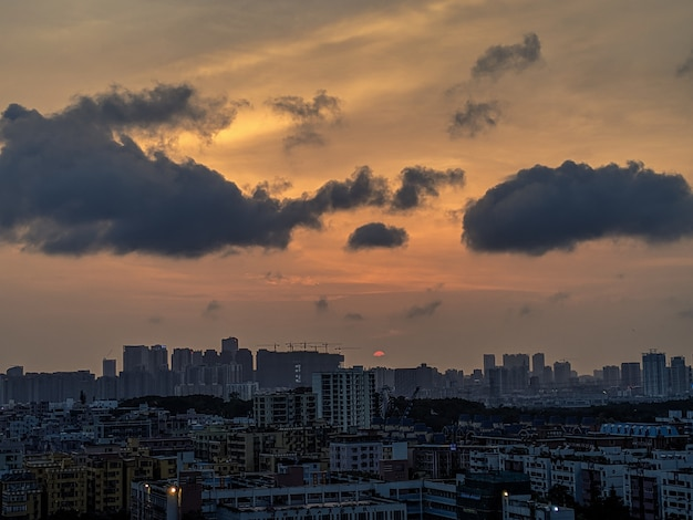 Wide shot of a modern and busy city with dark clouds and orange sky