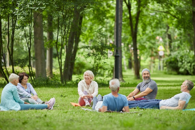 Wide shot of modern senior people spending summer morning together relaxing on grass in park after exercising