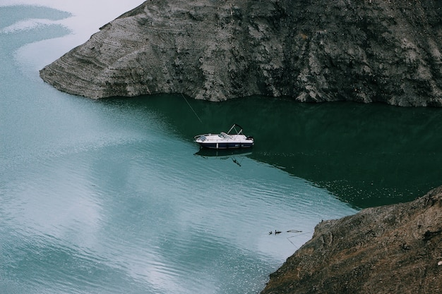 Wide shot of a motorboat on the body of water in the middle of mountains