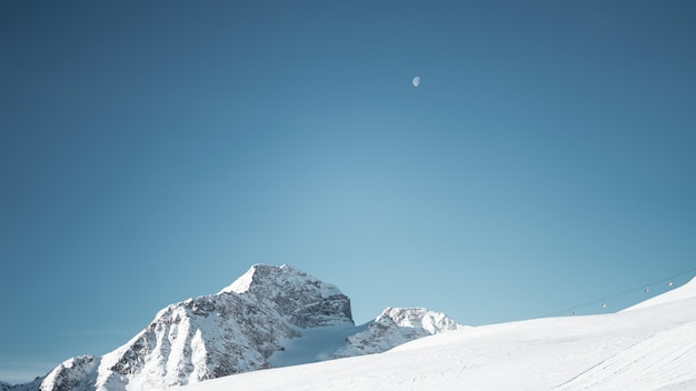 Wide shot of a mountain covered in snow under a clear blue sky with a half moon