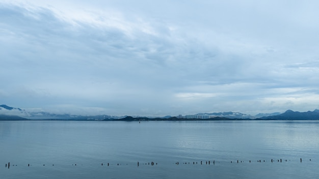 흐린 날에 산이 내려다 보이는 잔잔한 바다의 와이드 샷