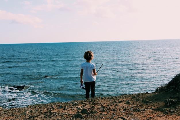 물 근처 해변에 서있는 작은 아이의 넓은 샷