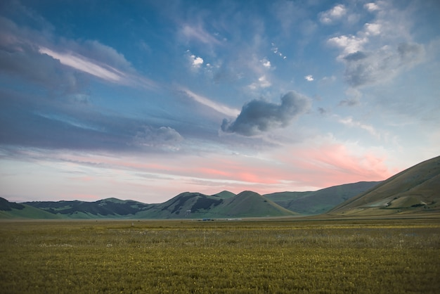 イタリアの色とりどりの曇り空の下の芝生のフィールドで美しい緑の山々のワイドショット