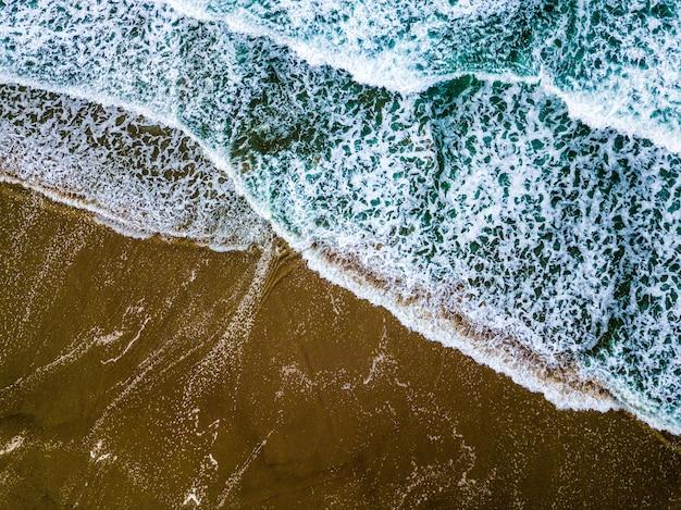 砂浜の海岸に青い海の波のワイドショット