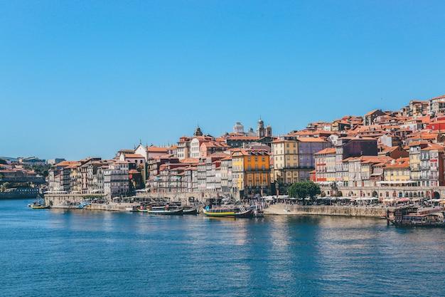 Широкий выстрел из лодок на поверхности воды возле домов и зданий в порту, португалия