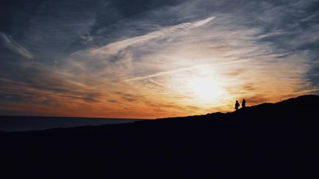 태양이 빛나는 언덕을 걷는 두 사람의 실루엣의 넓은 샷