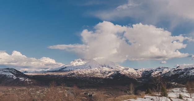 青い曇り空の下で遠くに雪に覆われた山のワイドショット