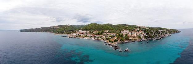 Общий вид побережья эгейского моря греции, построек лутры, расположенных у скалистых утесов, зелени и голубой воды. вид с дрона