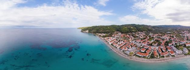 Общий вид побережья эгейского моря греции, построек скала фуркас, расположенных недалеко от скалистых утесов, зелени и голубой воды. вид с дрона