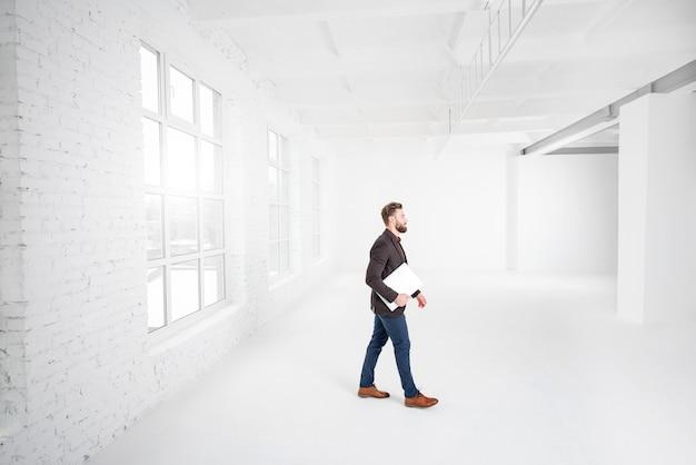 Интерьер белого офиса с бизнесменом, идущим с ноутбуком