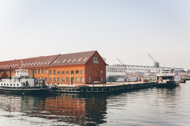 Широкий снимок белых яхт на водоеме возле порта с оранжевыми домами