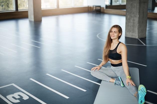 하드 필라테스 훈련 세션 전에 스트레칭 젊은 아름다운 피트니스 트레이너의 넓은 샷. 완벽한 건강한 신체 개념.