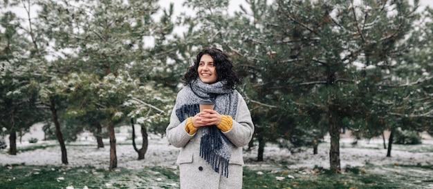 冬の雪に覆われた公園に行くためにコーヒーと一緒にフレイファッションコートと青いスカーフを身に着けている若い女性のワイドショット。