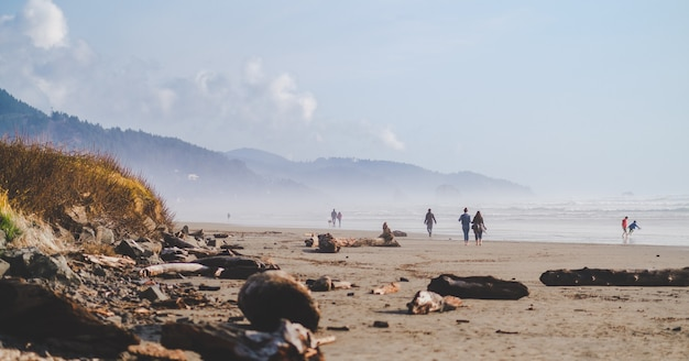 Wide shot of people walking on the beach shore with mountains in the distance at daytime