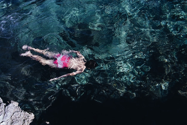 Wide shot of a person wearing pink and white swimsuit swimming in a clear sea