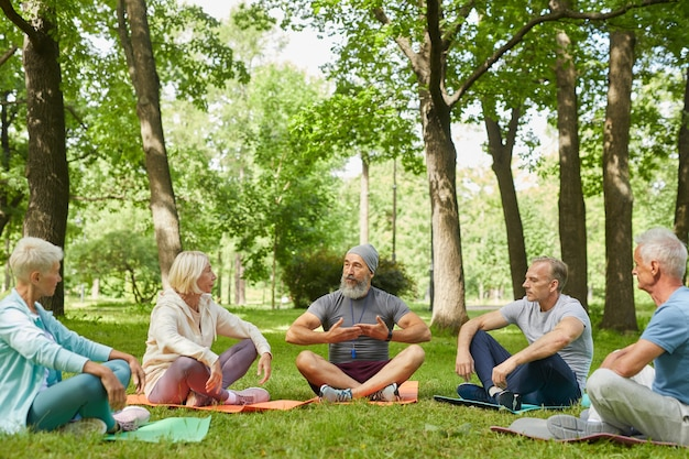 Wide shot of professional yoga trainer demonstrating his senior clients how to do breath exercise