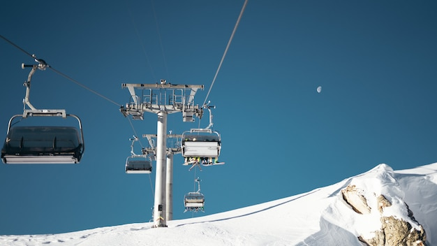 Wide shot of ropeways and gray pillar on a snowy surface under a clear blue sky with a half moon