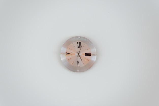Wide shot of a rose gold wall clock on a white wall