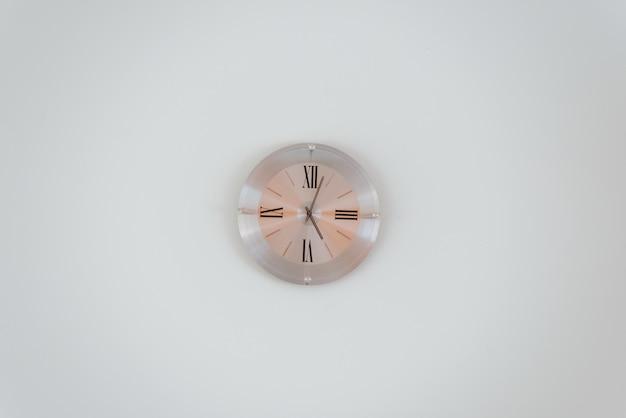 Panoramica di un orologio da parete in oro rosa su un muro bianco